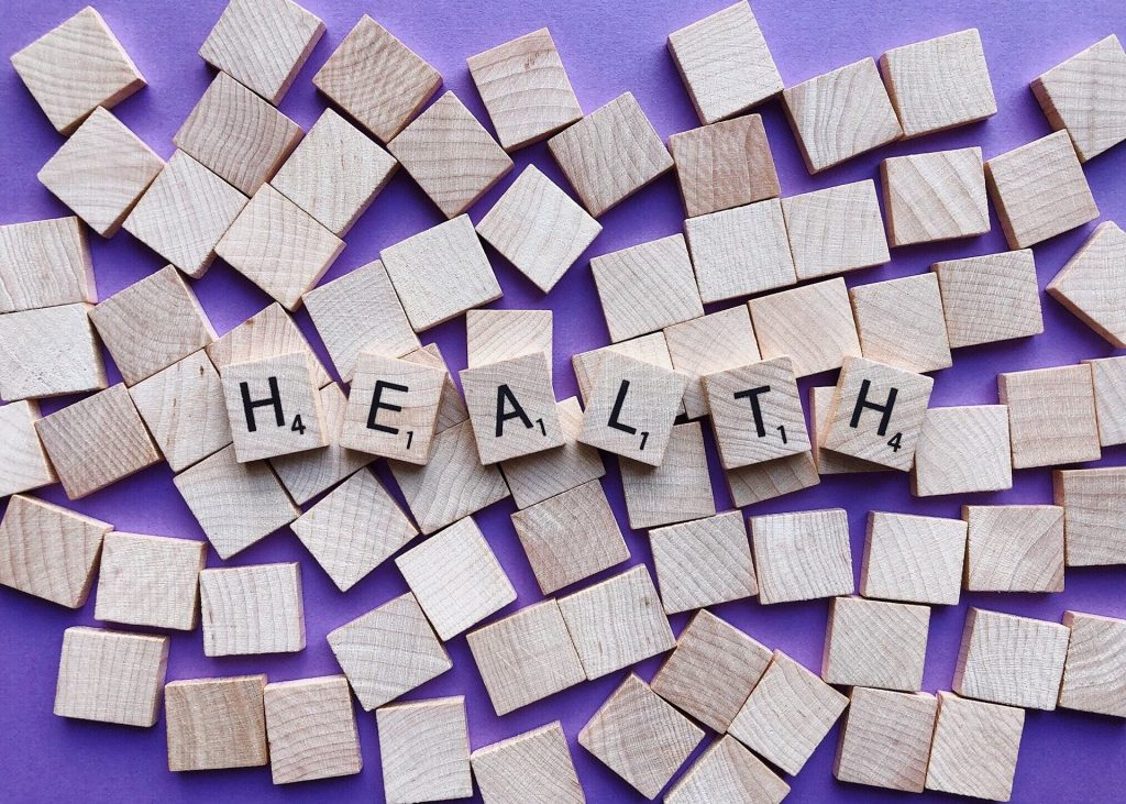 Image shows the word health in scrabbles tiles on a purple background
