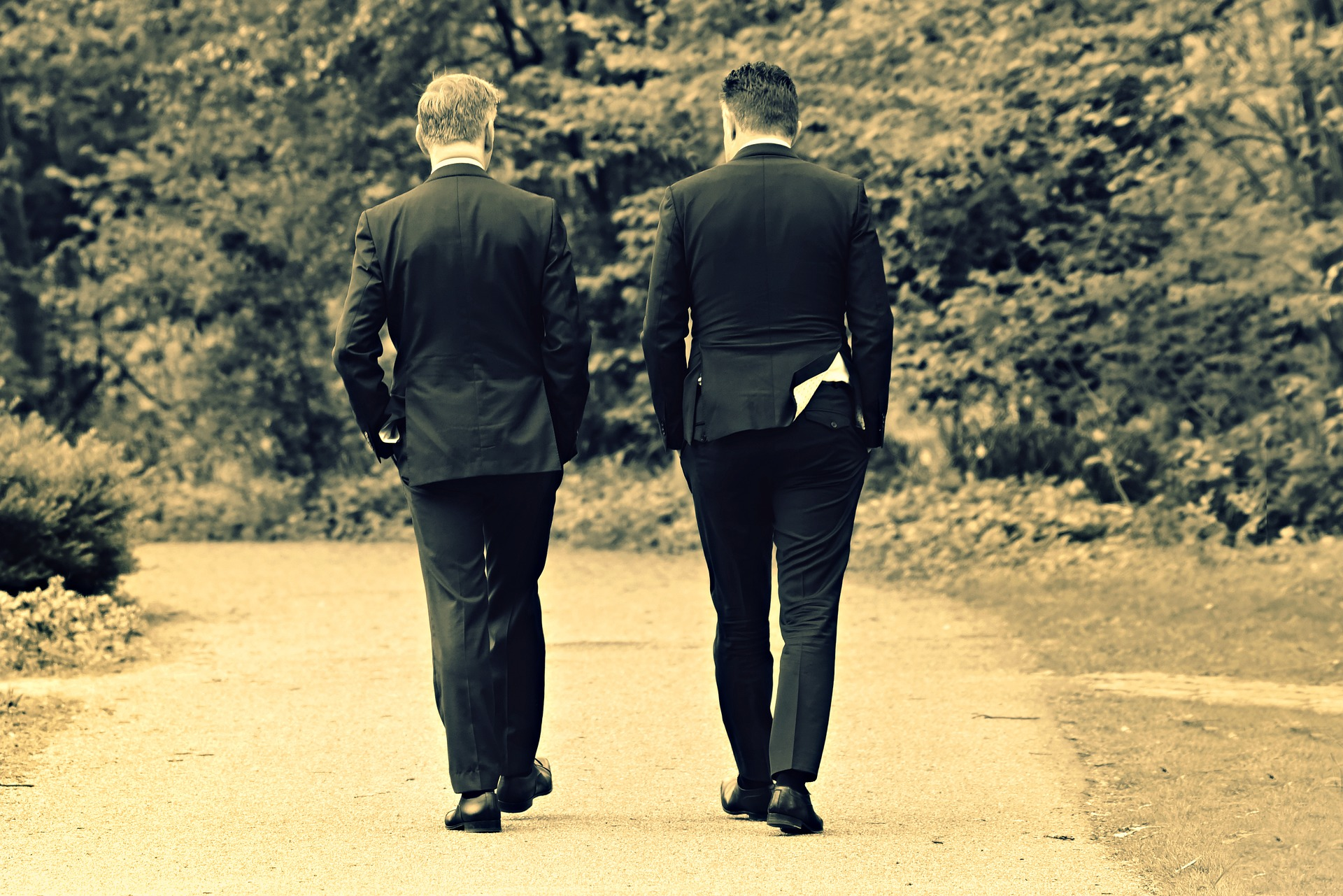 Images shows the back of two men in suits walking in a park