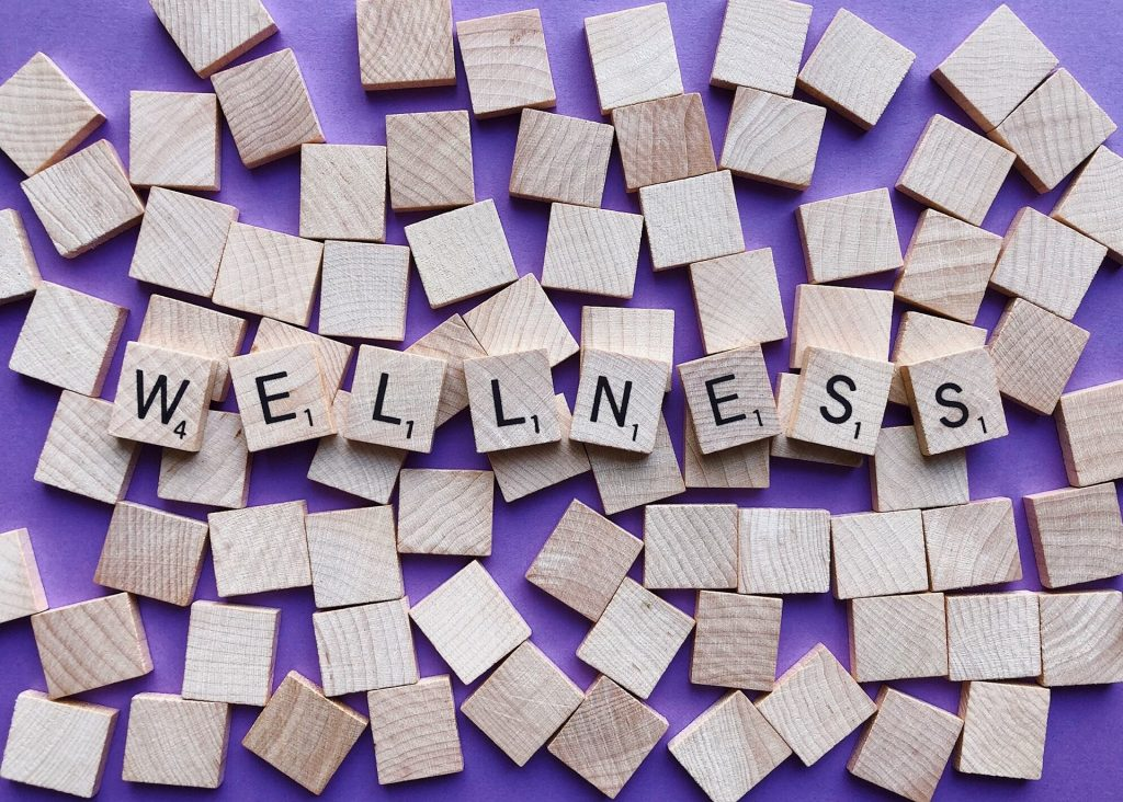 Image shows the word wellness in scrabbles tiles on a purple background
